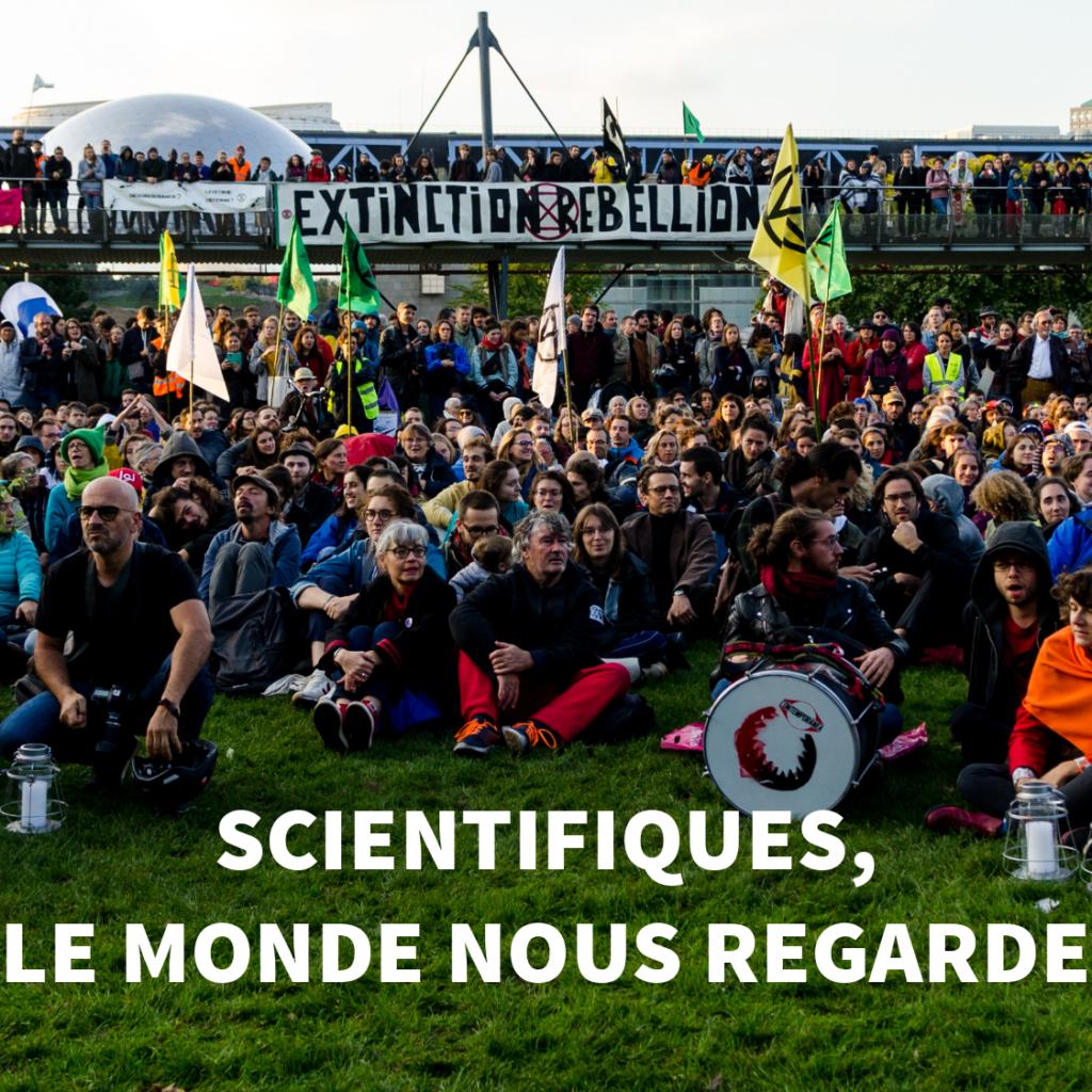 Image du rassemblement d'extinction rebellion a paris, titre en blanc : Scientifiques, le monde nous regarde